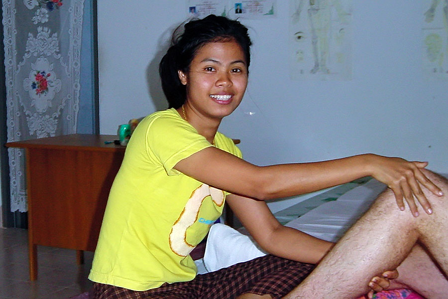 Young masseuse in a Thai massage shop working on my legs
