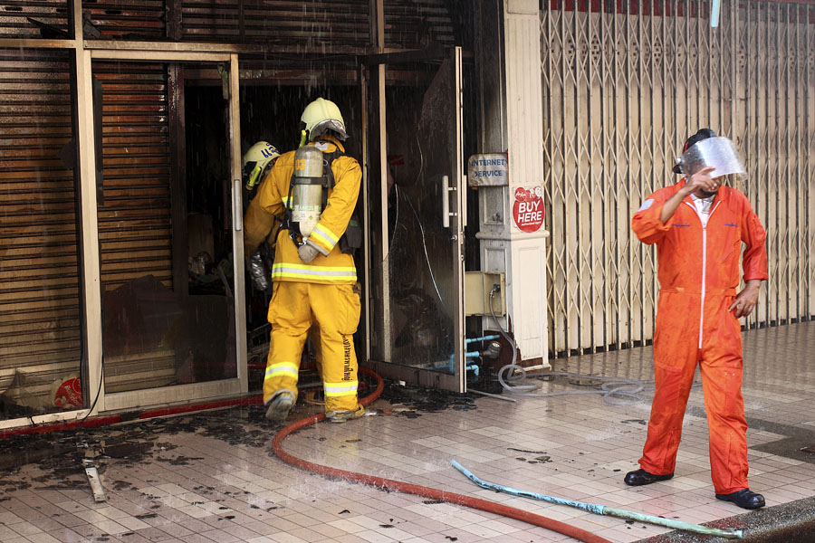 Firefighters with breathing apparatus checking for people inside, Hat Yai, Thailand